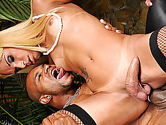 Caramel skinned blond T-Girl loves ebony men, she approaches the waiting stud and throws herself at him. He bends her over to slap her ass, pulling off her thong and spitting on her ass. With his fingers deep in her ass he grinds his palm against her cheeks. Holding on to her own cock she wraps her lips around his boner and deep throats his entire shaft. He sits back on the chair and pulls her onto his lap, easing his dick between her ass cheeks. Wanting more hip action he bends her over the chair and thrusts deeper into her ass. As she cums all over her chest, he explodes into her mouth.